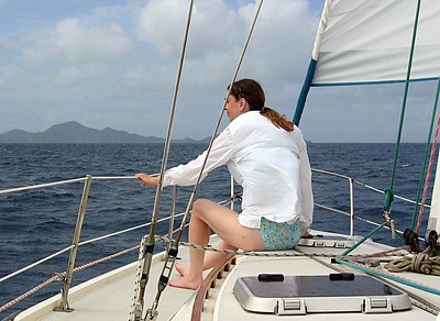 Daphne sitting at the bow of Fortitude   (Jul 20, 2004, 09:58am)  The morning of July 20th and we sail from Union Island to Sandy Island (a distance of around 5 miles), just north of Carriacou (which is actually part of Grenada).  Here you see Daphne riding up in the front of the boat.  The island in the distance is Carriacou.