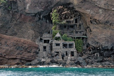 """Moonhole on Bequia   (Jul 19, 2004, 11:08am)  This is a picture of the famous """"moonhole"""" development on Bequia's south shore.  Moonhole was a natural development build in the 1960's. The dwellings were made of nothing but stone, wood and whalebone (no windows, only openings in the stone).  This is a picture of the original moonhole house.  It was named because the full moon would set, twice a year, though the hole in the natural arch.  Rumor says that the development was abandoned after a large rock came crashing through the bedroom ceiling."""