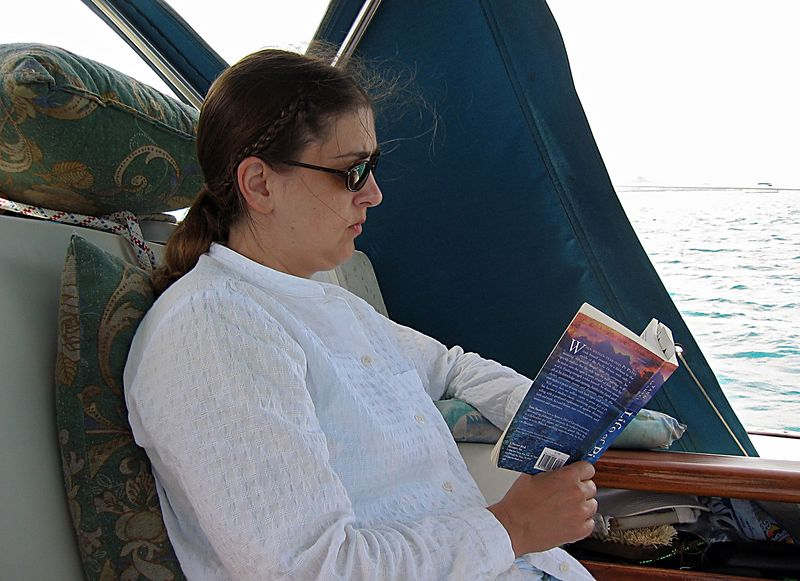 <b>Daphne reads Life of Pi</b>   (Jul 22, 2004, 09:40am)  <p align=left>Reading is a big activity for us during our vacation, including out time on Fortitude.  Here Daphne reads a few more pages between breakfast and our morning snorkel trip.  There is a story behind this book, Life of Pi; but you will have to read our travel journal to get the scoop.</p>  <p align=left></p>