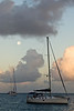 Sailboat and full moon at sunrise