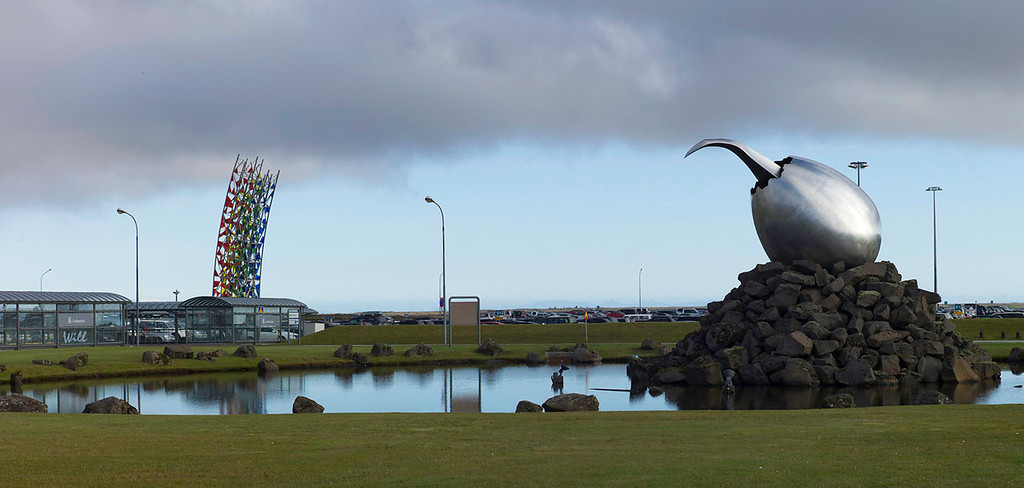 "© Robert Will 2013<br /> <br /> Iceland's Keflavik International Airport features 2 sculptures. <br /> <br /> On the left is ""The Rainbow"" by Rúrí made of stainless steel and stained glass. On the right is ""The Jet Nest"" by Magnus Tomasson.<br /> <br /> Keflavik is hugely controversial to native Icelanders. The airport and surrounding town were built by Americans during WWII and subsequently transferred to NATO. Icelanders deeply resent this ongoing military occupation of their country."