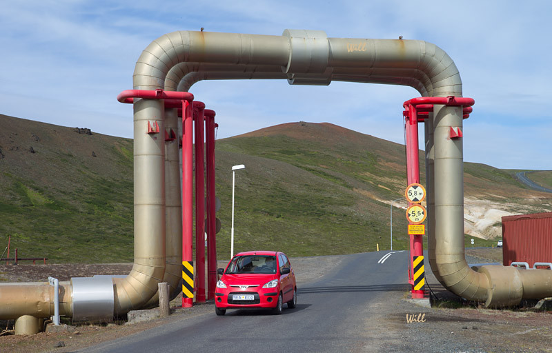 Pipes arch above the road at the Krafla Geothermal Power Station.