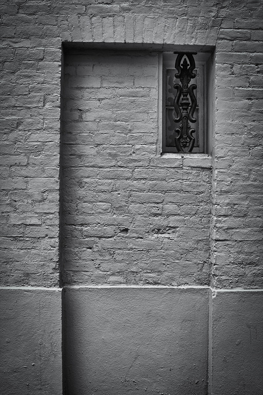 Brick wall with small window, French Quarter.