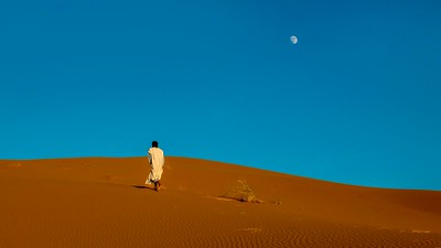 A Moroccan man walks uphill toward the ridge of a sand dune.