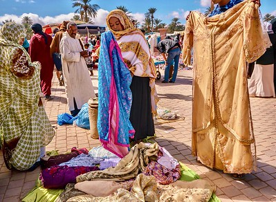 Marrakech, Morocco - October 24, 2015. Showing an outdoor market in a suburban area of Marrakech, where Moroccan shoppers are looking at clothing being sold by a street vendor.