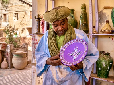A Moroccan salesman explaining the process of making pottery outside a workshop which is regularly visited by foreign tourists.