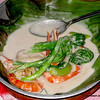 This shrimp dish is cooked with vegetables and coconut milk. It is served over banana leaves.