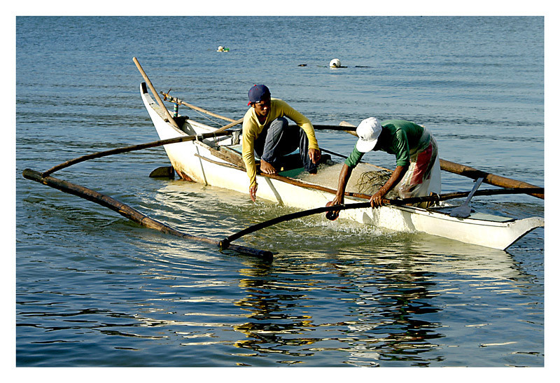 another pair of fishermen after they have brought up their net.