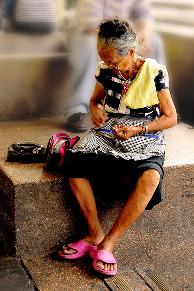 An old lady sits down to rest and count her loose change.