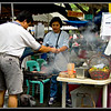"Babecued or grilled foods (called ""Inihaw na Pagkain"" in Pilipino language) are very popular at the farmers market. I took photos of people grilling food over wood charcoal. This is one of the two. As the sign says, the woman is selling beef kabab. There is also a sign that says, ""Cebu Lechon"". Lechon is roasted pig over charcoal. Cebu is a southern city in the Philippines. One side of this farmers market is set aside for dining. Although the dining area is under the trees, they provided a roof to protect you from rain. people come here instead of going to the restaurants. The food is fresh and it is more inexpensive. It is similar to the market dining of Singapore and Vietnam. Photo was taken in January 2006."