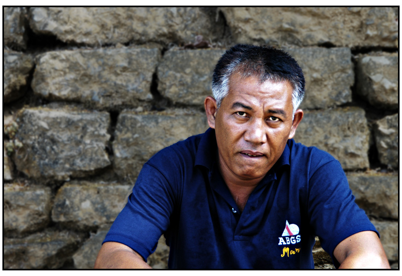 """<FONT size=""""-1"""">This is the photo of a tired former Philippine Navy soldier visiting the island of Corregidor. It was very warm. I saw him sat down on the curb with a stone wall behind him. I talked to him about Corregidor. He said his father died defending this place from the Japanese invasion. I asked him if I could tke his picture. He smiled said yes and bit his lips. So I took it. Taken 2005-05-11."""