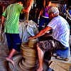 As the potter shapes the clay another man continously kicks the wheel to go around.