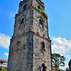"A few meters away from the church is the coral-stone bell tower which served as an observation post of the ""katipuneros"" during the Philippine Revolution and again by the guerillas during the Japanese occupation.<br /> <br /> According to historians, the bell tower also served as a status symbol for the locals. The bell would ring more loudly and more times during the wedding of a prominent clan that it would during the wedding of the poor."