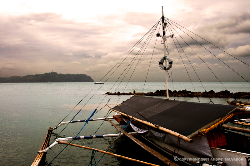 This was taken before sunset, but the sky was overcast. Only the intense glow of the sun gives an eerie light on the port of Jaro. An outriggered boat that plies the water between Jaro and Guimaras had been prepared for the rain predicted to come that night. Tarpaulins have been rolled down the side of the boat to keep the seats dry.