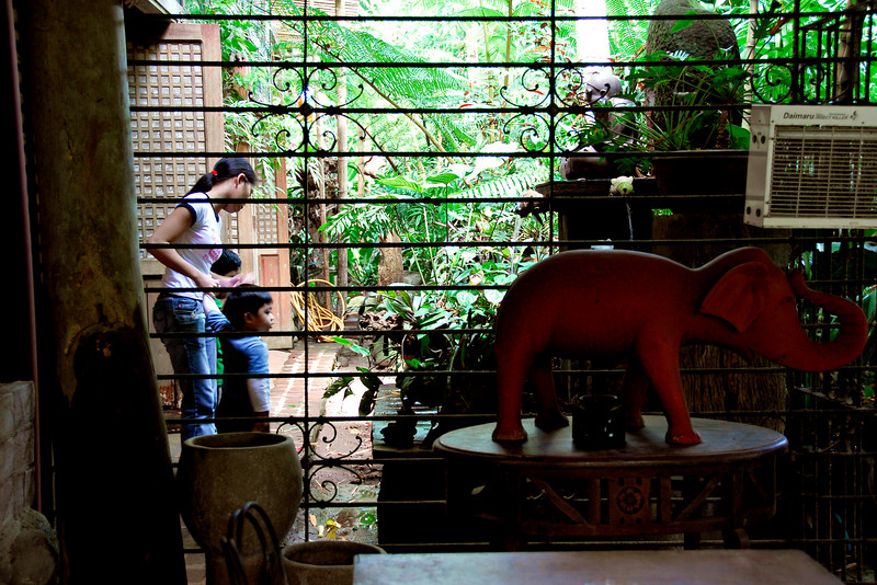 The children cannot satisfiy their curiosity as their yayas (nannies) stop them from roaming beyond the dining room.<br /> <br /> This area in the foregrond seems to have a very eclectic interior design or just an area where the owner stores surplus decorative items.