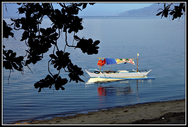 It is still early in the morning about seven o'clock and there are no one around on the beach except for a lone boat.