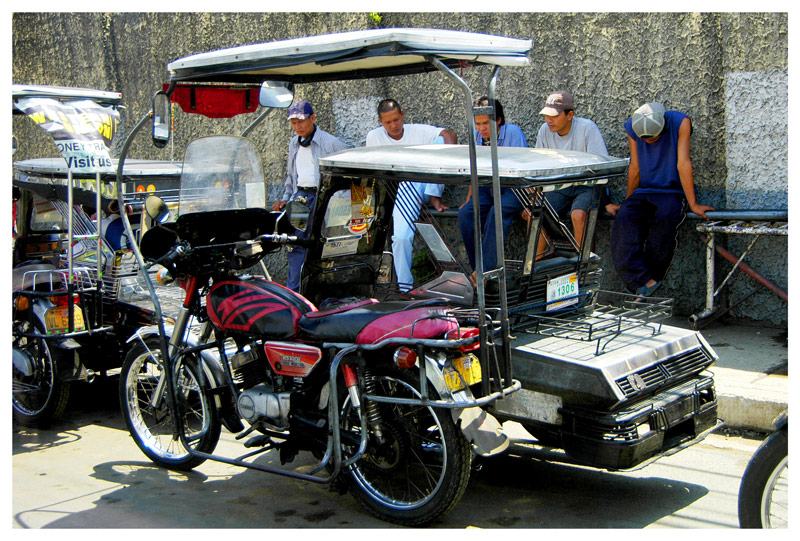 A tricycle and the drivers waiting for passengers under the shade of a cncrete wall. Taken in Lipa City, Batangas.