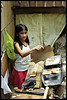 A young eleven year old girl helping her Mom grill bananas. The long machete is for removing the husk of the coconuts.