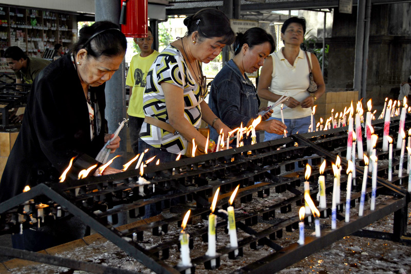 View of people offering candles at the candle offering area.