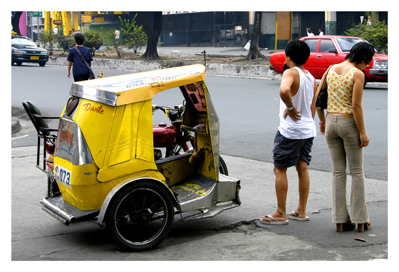 The woman just came off the tricycle while the tricycle driver is helping her flagged down a taxicab. Taken at Quezon Boulevard.