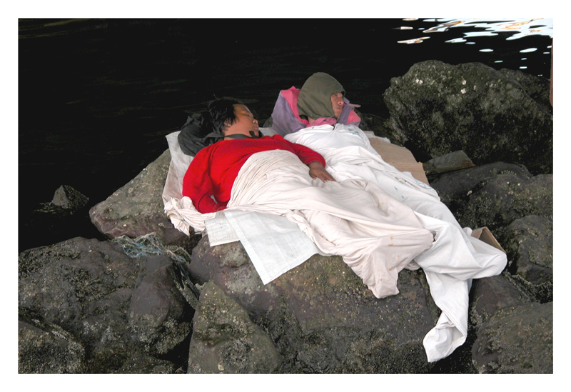 These couple find sleepng on the rocks by the water a cooling experience, that is the good part. The couple is homeless, that is the bad part.