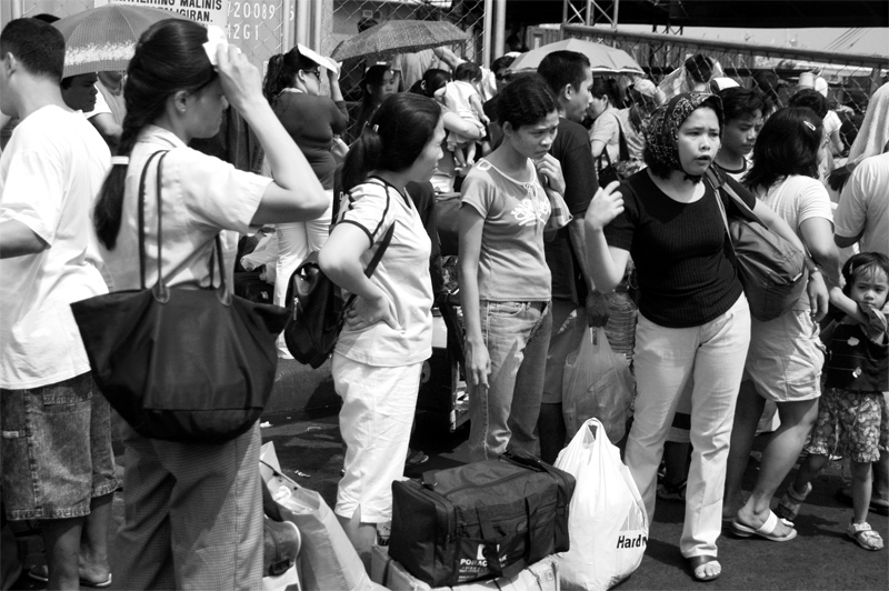 These are the passengers of the ship that just arrived. They are all waiting for a bus or relatives to pick them-up. It is very chaotic as vehicular traffic mixes with pedestrian traffic. Taken at Manila North Bay Pier.