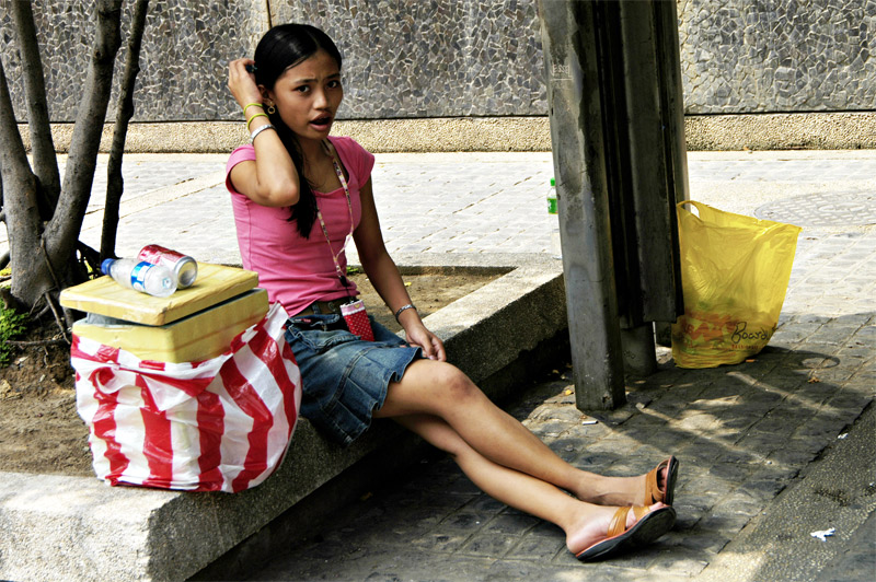 For a sidewalk vendor, she is very pretty. The food she sells are insulated by the styrofoam box container.