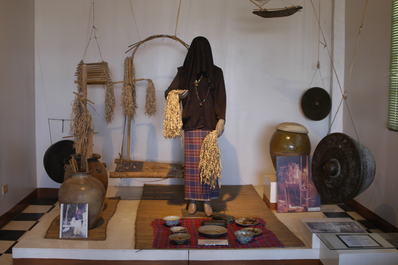 This was taken inside the museum. This set depicts a woman in mourning holding some bamboo shavings to hit herself with as a sign of mourning and penitence. the steel drums are for the music and the jars are for the ashes after cremation.