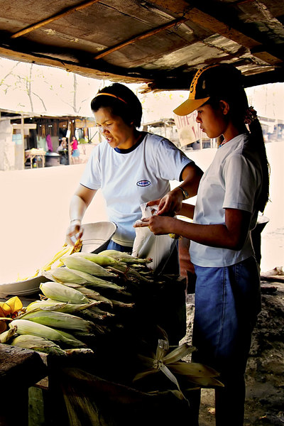 A mother and daughter helping each other in preparing the corn for cooking at one of the roadside stand.