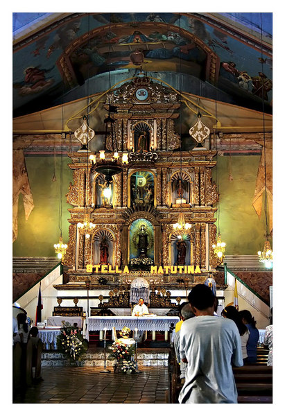 The altar of Baclayon Church of ornate 3-tier retablo design.