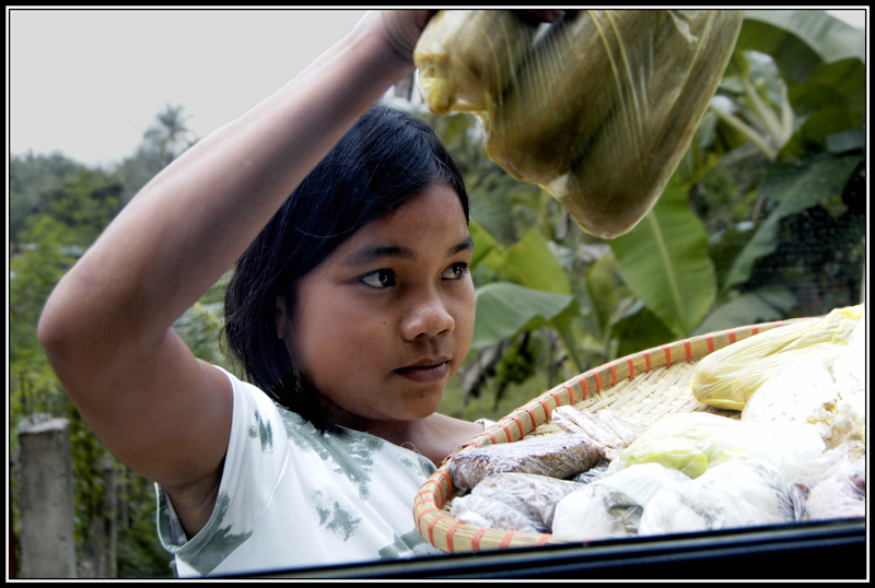 A young teenage girl peddling steamed sweet corn and Pilipino rice pastries while we were inside our van.