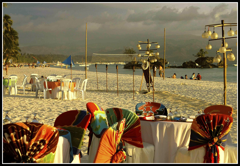 In the hotel we stayed in, the dning tables and chair are set-up at sunset. As soon as the sun goes down the food table is brought out and you may start having dinner. Capiz shell lamps on bambbo posts are placed into the sand for lighting.