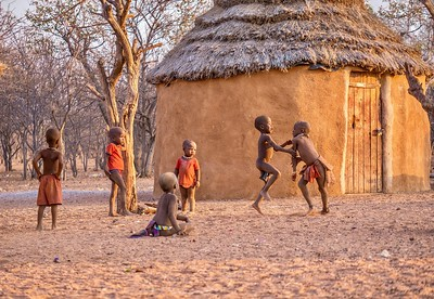 A group of happy boys play together near a mud house in their African Himba tribal village in Namibia.