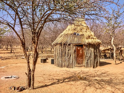 A traditional style African house in rural Namibia combined with modern technology. The walls are made from branches and mud, but solar panels sit on its thatched roof.