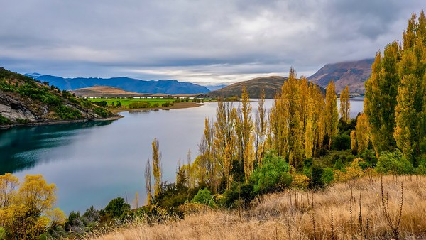 A panoramic view of a beautiful freshwater lake in autumn, surrounded by rolling hills and rural farmland, on the South Island of New Zealand.