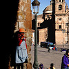 An Incan woman waiting at the side of the Cathedral. Part of the church La Compania de Jesus is on the right.