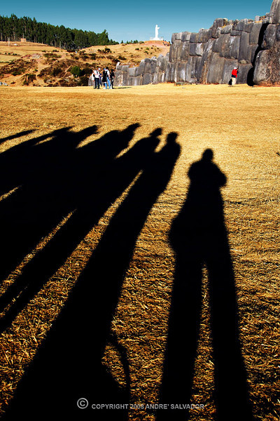 This was taken at Saqsaywaman Archeological Site in Cusco. Our group just entered the huge grounds of Saqsaywaman when it was almost sunset. I noticed our long shadows while we were all lined up admiring the the ruins. Our long shadows were all pointing to the Royal House of the Sun ruins. Beyond us is the peak or highest point of the mountain with the statue of Jesus Christ that looks down on the city of Cusco. The ruins are built at a lower level around it.