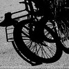 The bicycle's shadow play on the sidewalk attracted my attention.