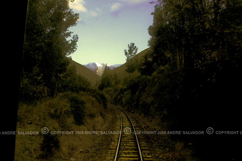 The railway was dark but the snow capped mountain beyond is already bathed in sunlight.