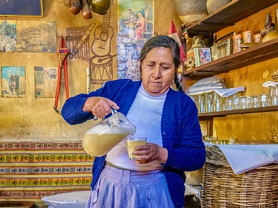 Chicha, the traditional fermented Andean drink made from maize, being poured by a Peruvian woman in a chicha tavern known as a chicheria.