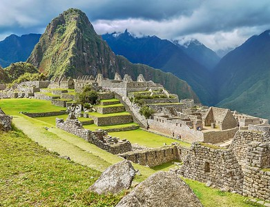 A close-up view of the ruins and vibrant green terraces at the base of Huayna Picchu mountain