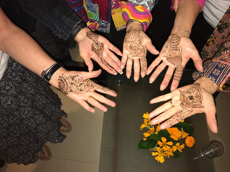 Daisy paints the ladies hands with Henna.