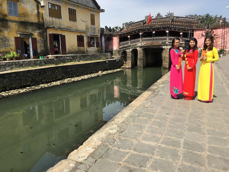 Hoi An Japanese bridge. Local girls pose for photographer