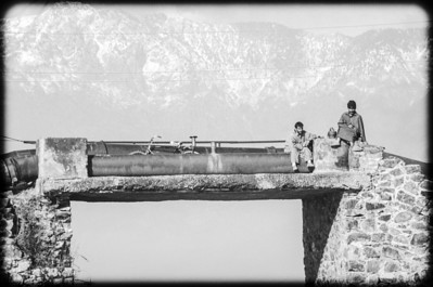 Kashmiri men on water pipeline, bridge above Dal Lake