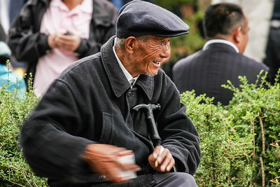 Local old man sitting at the squares reaching for a cigarette.