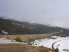 Empty train tracks appear to lead to nowhere. The snow is starting to fall as the fog moves over the mountain tops.