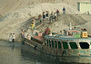 Manpower - unloading a boatload of sand by hand