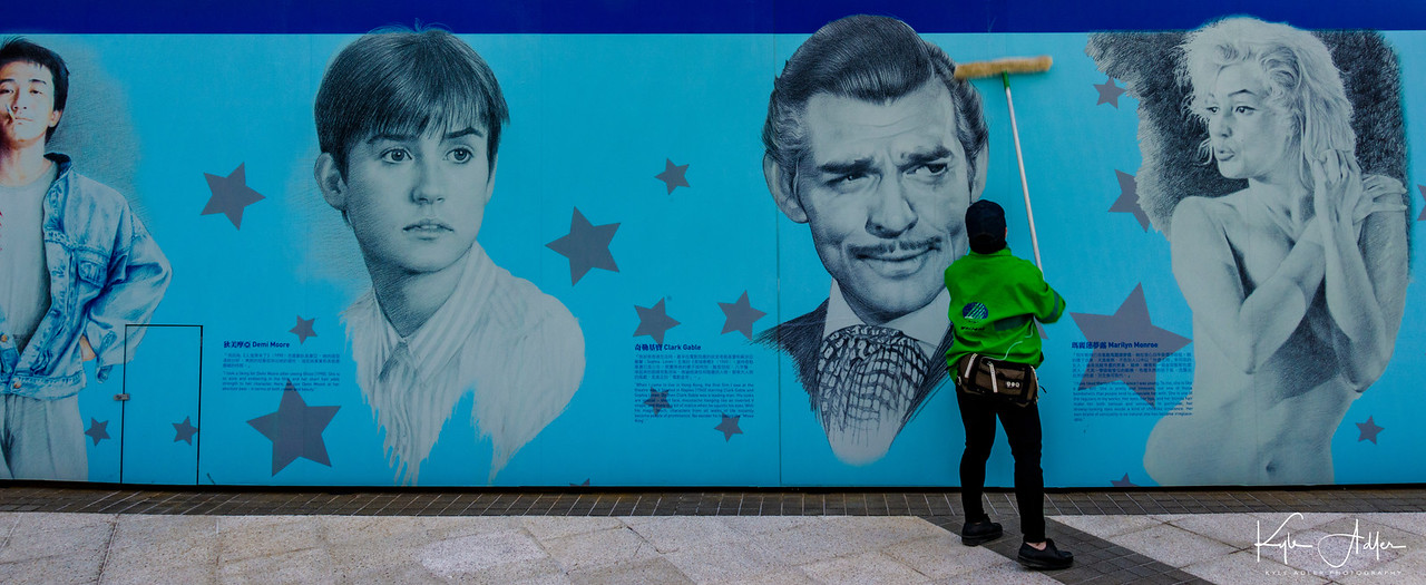 Hong Kong's take on the Hollywood Walk of Stars features a mix of western and Chinese movie stars.  This piece of street photography includes a live human cleaning the mural between the images of Clark Gable and Marilyn Monroe.