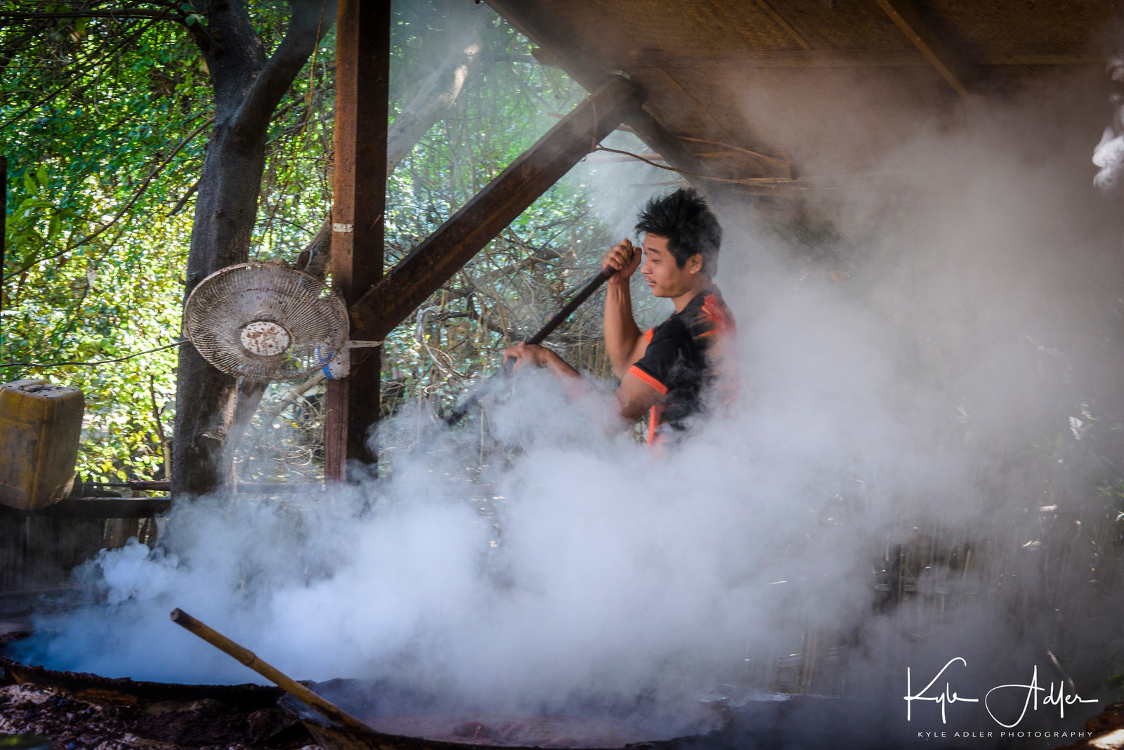 Escaping steam nearly obscures a worker at a Bagan workshop where pone ye gyi (a popular flavored soybean sauce) is made.