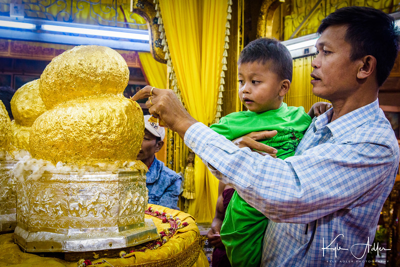Applying some gold leaf to the sacred Buddha statues at Phaung Daw Oo Paya.